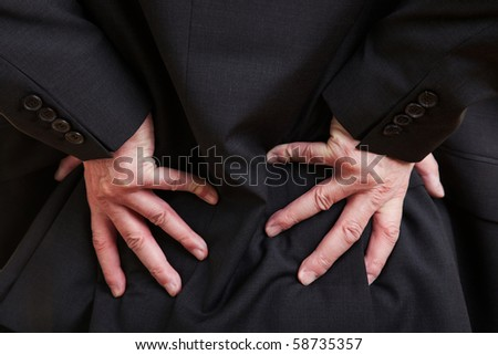 Elderly businessman holding his hand to his aching back