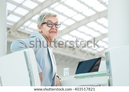 Elderly businesswoman in office - stock photo