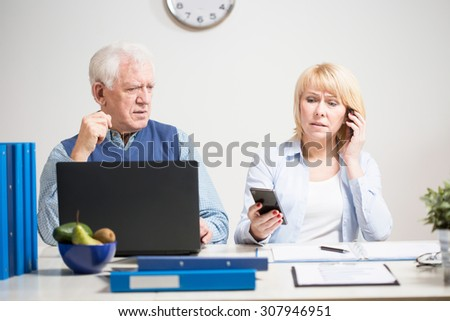 Elderly busy businesswoman with two mobile phones - stock photo