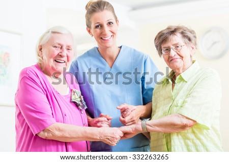 Elderly care nurse with two senior women - stock photo