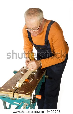 elderly carpenter is slicing the wood