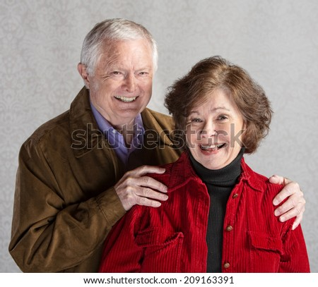 Elderly Caucasian couple laughing in front of gray background - stock photo