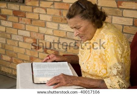 elderly caucasian female reading her bible - stock photo