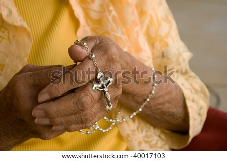 elderly caucasian hands holding a silver rosary - stock photo