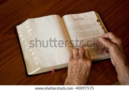 elderly caucasian hands over an open bible - stock photo