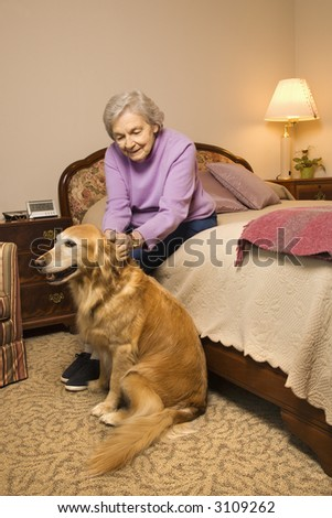 Elderly Caucasian woman and dog in bedroom at retirement community center. - stock photo