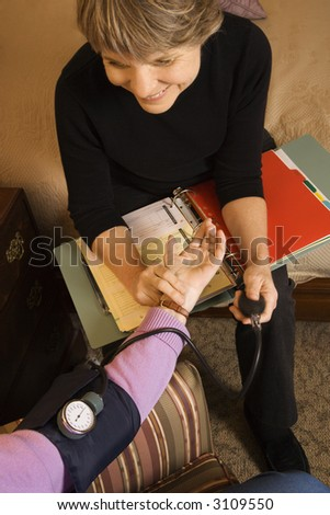 Elderly Caucasian woman at retirement community center receiving blood pressure test by nurse. - stock photo