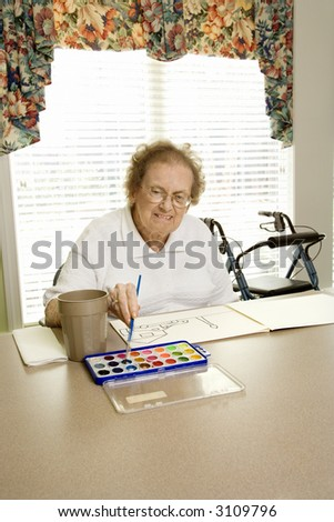 Elderly Caucasian woman painting with watercolors at retirement community center. - stock photo