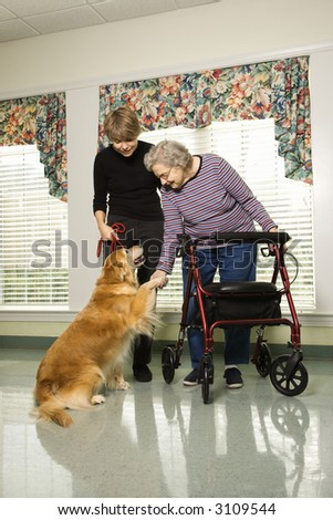 Elderly Caucasian woman using walker and middle-aged daugher petting dog in hallway of retirement community center.
