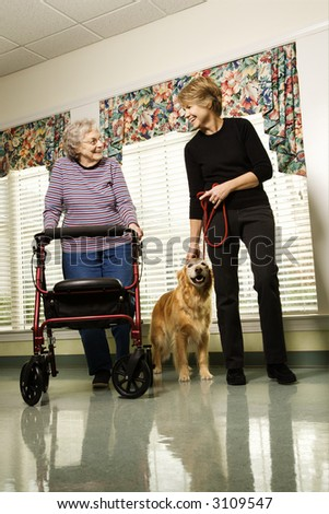 Elderly Caucasian woman using walker and middle-aged woman walking dog in hallway of retirement community center. - stock photo