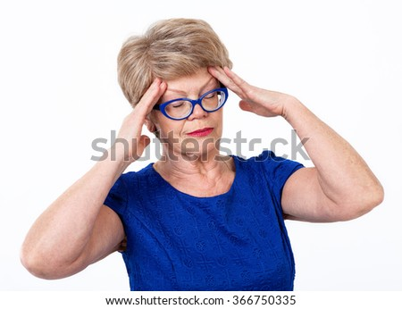 Elderly Caucasian woman with headache, holding her head with hands, closed eyes, white background - stock photo