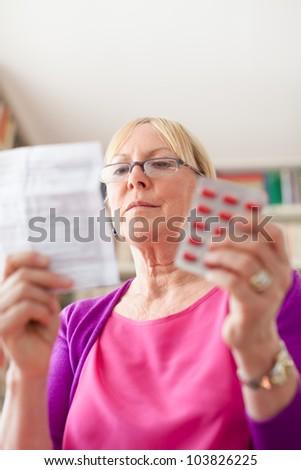 Elderly caucasian woman with medicine and reading drug prescription. Copy space - stock photo