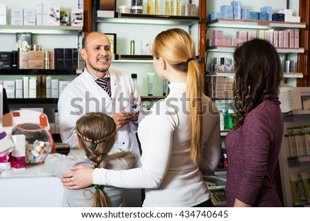Elderly cheerful male pharmacist in white coat working the pharmaceutical store and consulting customers - stock photo
