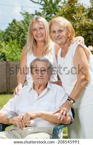 Elderly couple and their daughter outdoors - stock photo