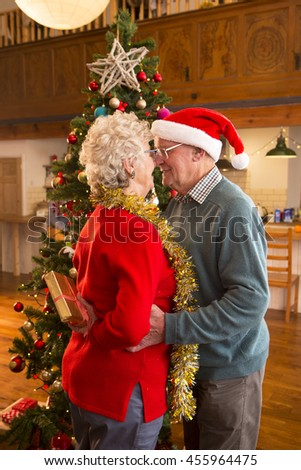 Elderly couple at Christmas. The lady has a present behind her back and has her nose touching her husband's nose. - stock photo
