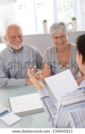 Elderly couple at financial consultation, smiling. - stock photo