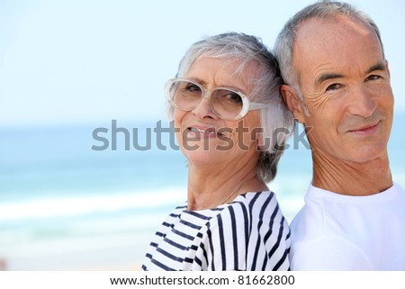 Elderly couple at the beach together - stock photo