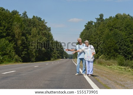 Elderly couple catching a car on a road - stock photo