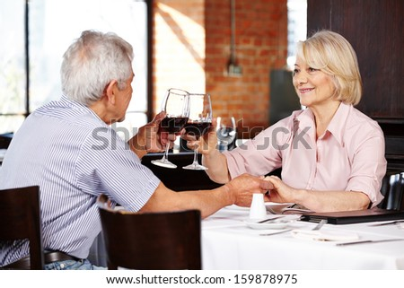 Elderly couple clink glasses with red wine in a restaurant - stock photo