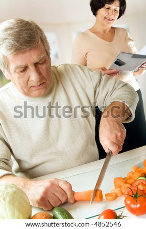 Elderly couple cooking at kitchen. Focus on man. - stock photo