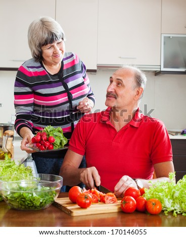 elderly couple cooking with fresh vegetables and greens in home kitchen