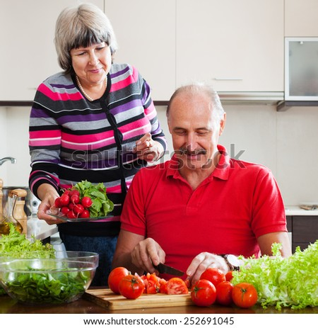 elderly couple cooking with  vegetables and greens in home kitchen