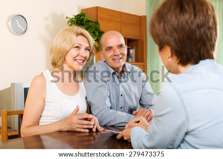 Elderly couple discussing details of private insurance with agent