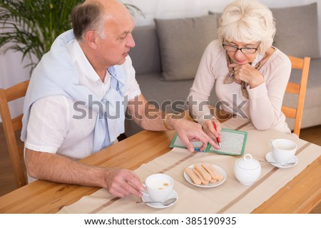 Elderly couple doing crossword and drinking coffee
