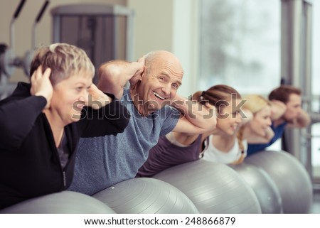 Elderly couple doing pilates class at the gym with a group of diverse younger people balancing on the gym ball with raised arms to tone their muscles in an active retirement concept - stock photo