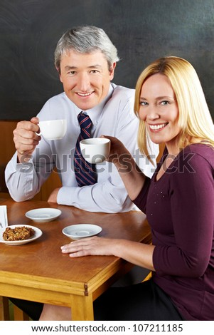 Elderly couple drinking coffee in caf�© with smile on their face