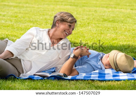 Elderly couple enjoying relax time in sunny park - stock photo