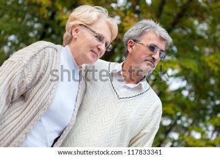 Elderly couple enjoying walk in the park - stock photo