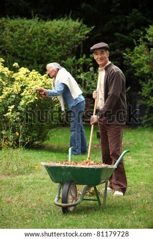 elderly couple gathering leaves - stock photo