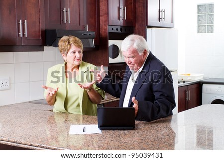 elderly couple having argument over expense - stock photo