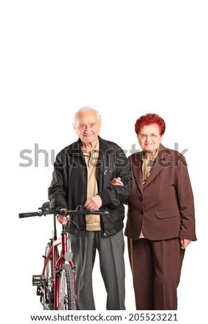 Elderly couple holding hands and pushing a bike isolated on white background - stock photo