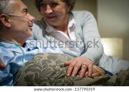 Elderly couple holding hands sick man lying in bed - stock photo