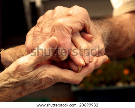 Elderly couple holding hands with love - stock photo