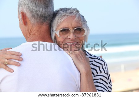 Elderly couple hugging by a beach - stock photo