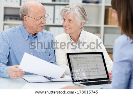 Elderly couple in a meeting with an adviser discussing a document as she watches across the desk in her office - stock photo