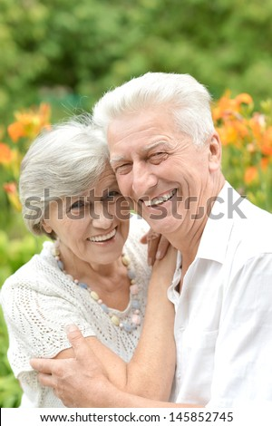 elderly couple in love walking in the park in spring - stock photo