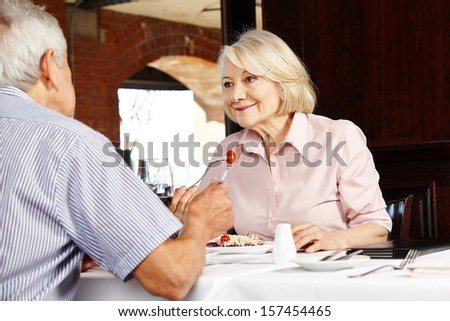 Elderly couple in restaurant talking to each other while eating - stock photo