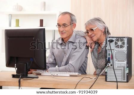 Elderly couple learning computer skills - stock photo