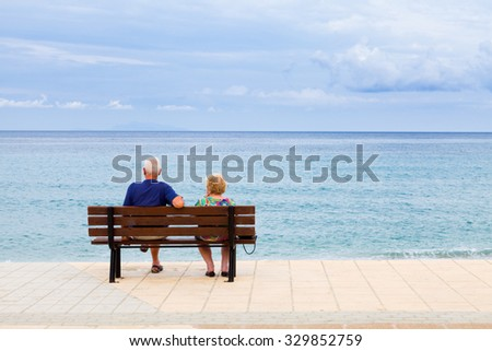Elderly couple looking to the sea in Greece, Kefalonia in a cloudy day - stock photo