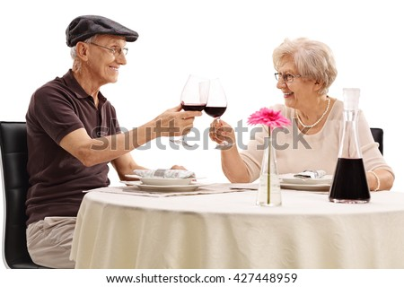 Elderly couple making a toast with red wine on a romantic date isolated on white background - stock photo
