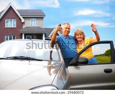 Elderly couple near their home.  Real estate and insurance concept - stock photo