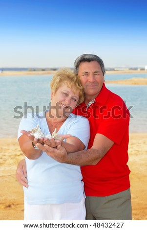 Elderly couple on the beach holding seashells and corals.