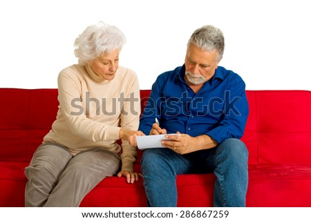 elderly couple on the couch writing - stock photo