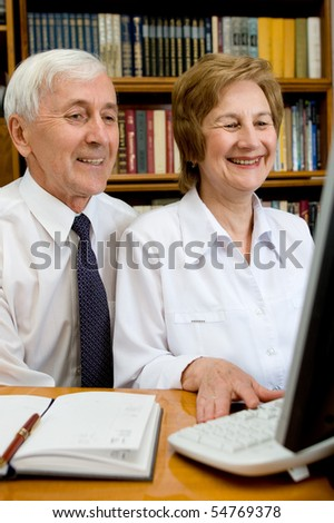Elderly couple peers into monitor of the computer a pleased smile upon one's face - stock photo