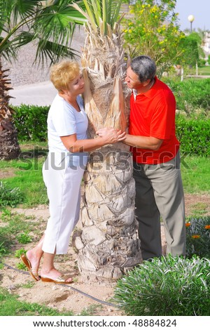 Elderly couple playfully looks at each other near the palm.