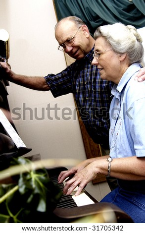 Elderly couple playing piano - stock photo